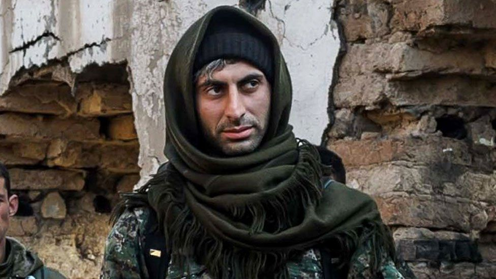 Johan Cosar is photographed in military fatigues with a scarf wrapped around his head