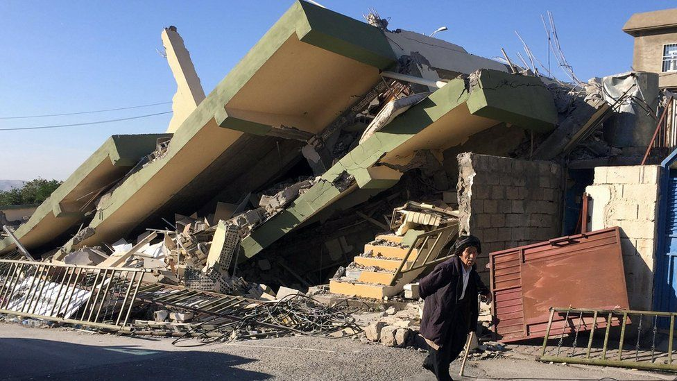 A man walks in front of a crushed building in Darbandikhan, Iraq