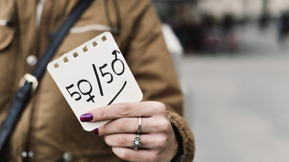 A woman in the street shows a paper with the text 50/50 written in it, with the zeros as the female and male gender symbols, depicting the gender parity concept.