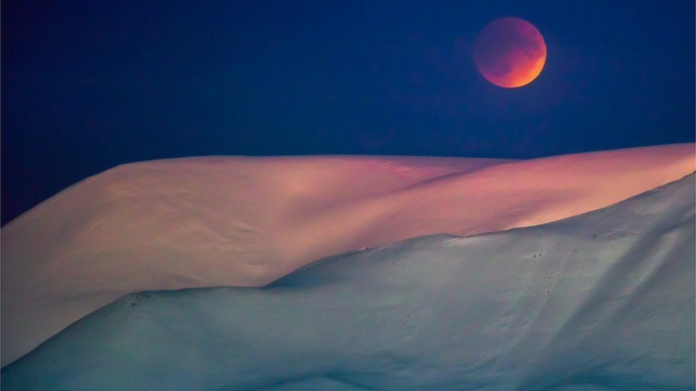A super blue blood moon behind a mountain is seen from Longyearbyen, Svalbard, Norway, against a violet sky