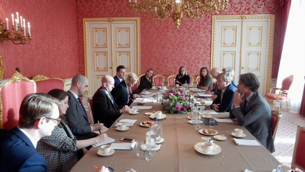 Journalists sit around a table in a grand setting of the Dutch royal palace, with the king in their midst