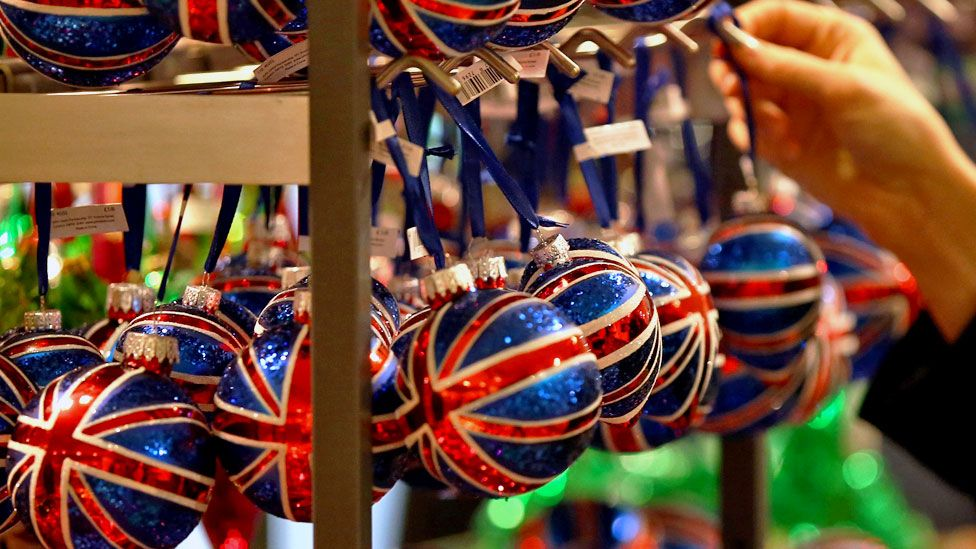 A customer looks at Union Jack decorated Christmas tree baubles in a John Lewis department store
