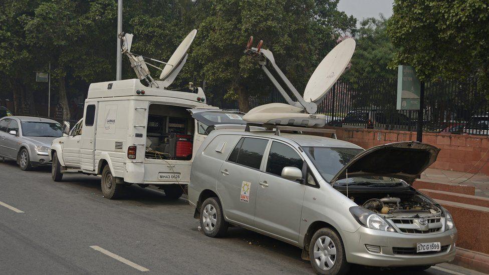 TV satellite vans parked in street in Delhi