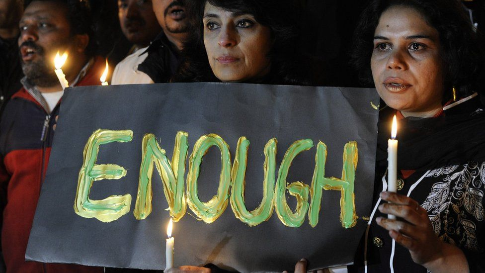 Pakistani journalists holding up sign with the word ENOUGH on it, light candles to pray for the victims who were killed in an attack at the Army run school in Peshawar, during a memorial ceremony in Islamabad Pakistan, 16 December 2014.