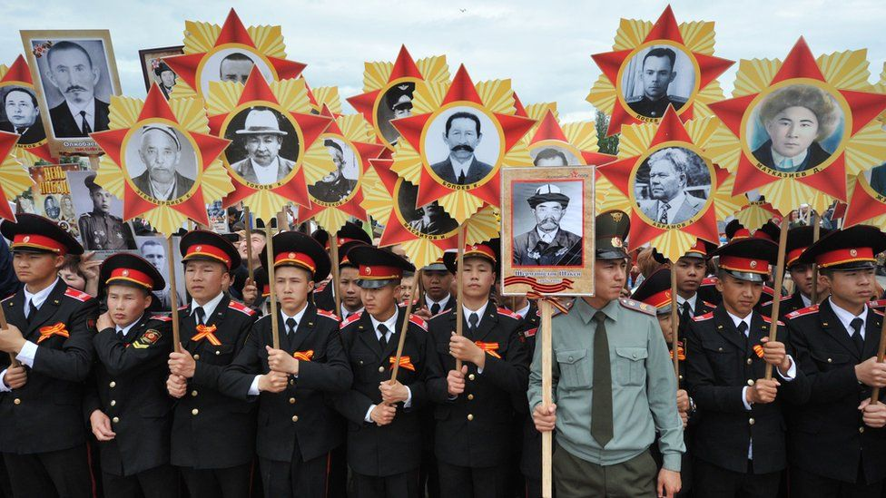 Kyrgyz military cadets hold portraits of World War Two soldiers as they take part in the Immortal Regiment march in Bishkek on May 9, 2016