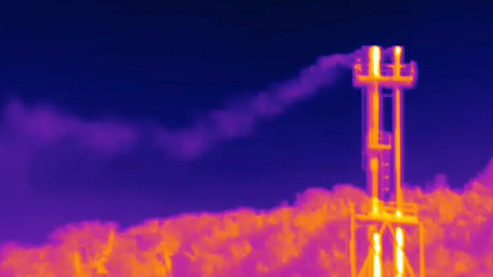 An infrared camera captures what appears to be methane escaping from a natural gas facility