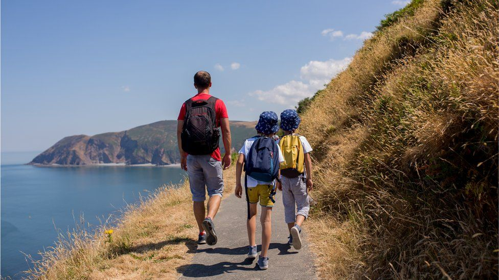A father and two boys walk along the Devon coastline