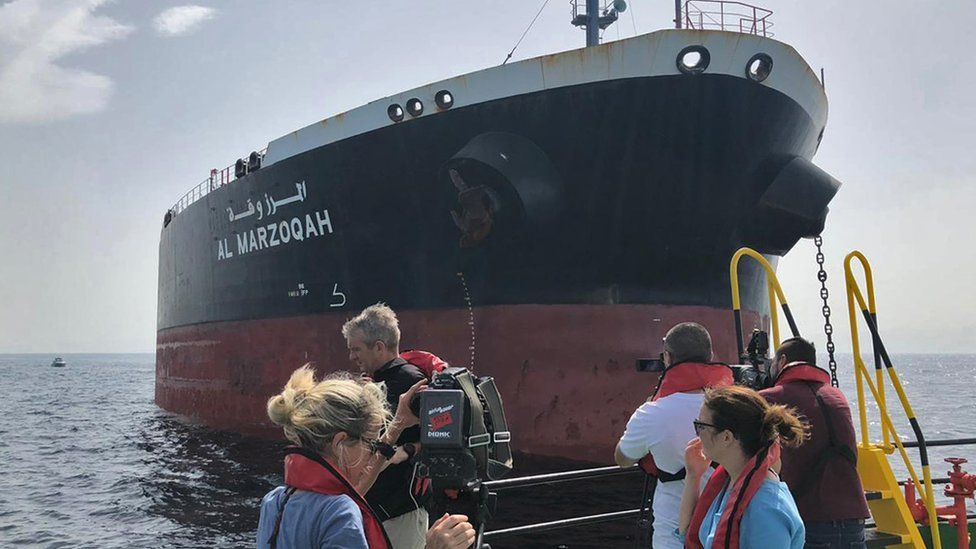 Journalists view the damaged Saudi oil tanker Al-Marzoqah in the Gulf, 13 May