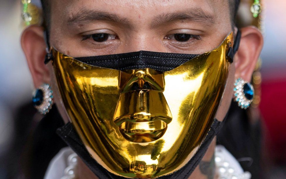 A person wears a golden face mask