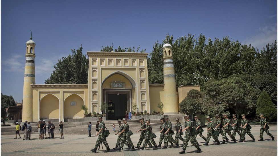 Security forces march past the Id Kah mosque in Kashgar in July