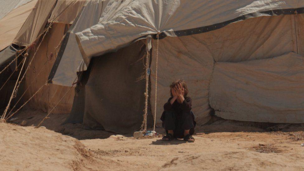 Criança fora de uma tenda