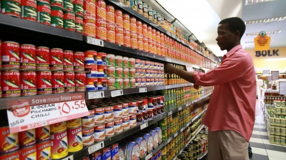A Zimbabwean shop worker displays food cans in a supermarket in Harare (13 October 2010)
