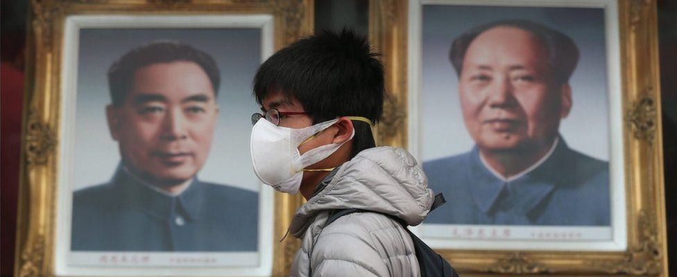 A Chinese man wearing a mask walks by portraits of former Chinese leaders Mao Zedong (R) and Zhou Enlai in a shopping street during a hazy day in Beijing city, China, 22 December 2015