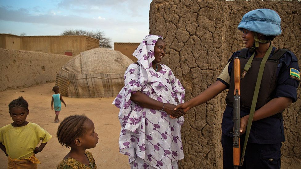 A peacekeeper shaking the hands of a woman in Mali