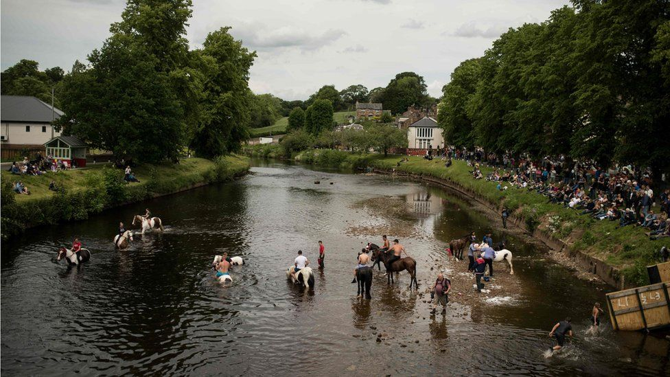 People wash horses in the River Eden on the second day of the annual Appleby Horse Fair