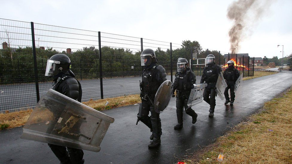 Police in riot gear protected contractors as they tried to remove bonfire material