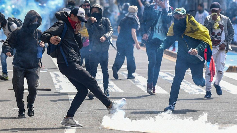 Demonstrators confront riot police during a protest against the government in Bogota