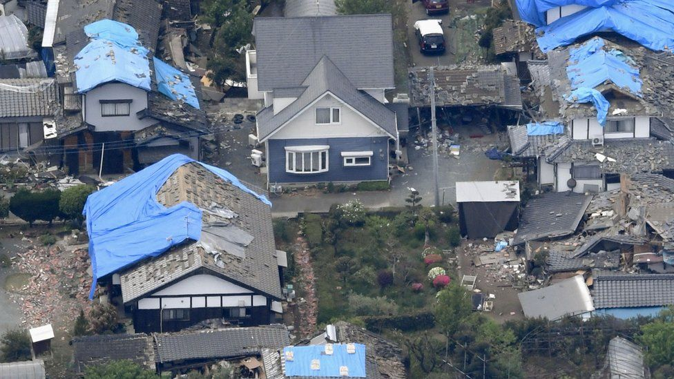 Blue plastic sheets are used to cover damaged roofs in Mashiki, Kumamoto prefecture, southern Japan (16 April 2016)