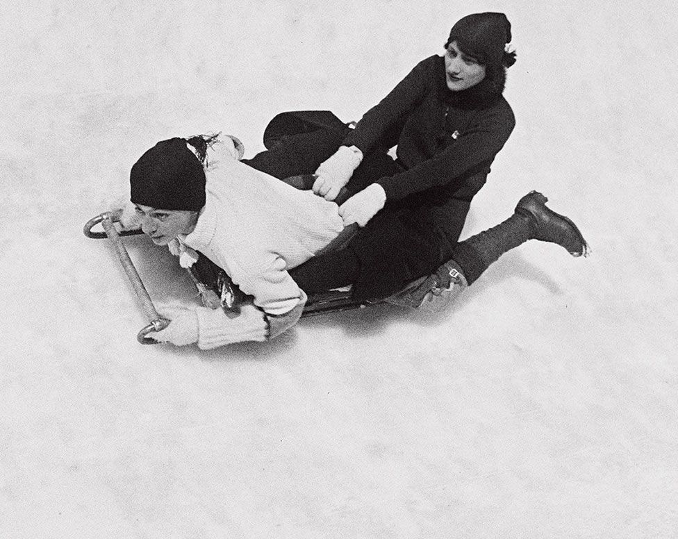 A young man and woman fly sledge down a snow-covered slope