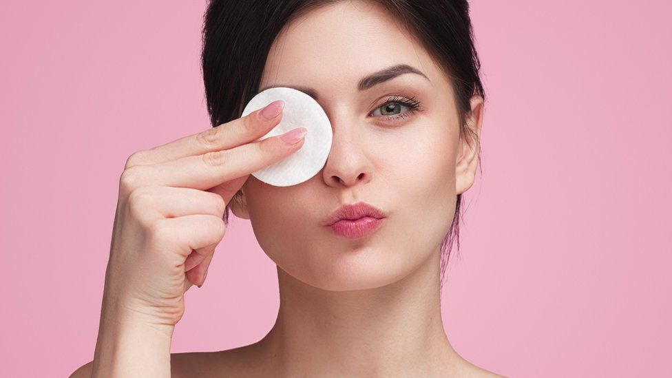 Stock image of a woman using a cotton make-up removal pad
