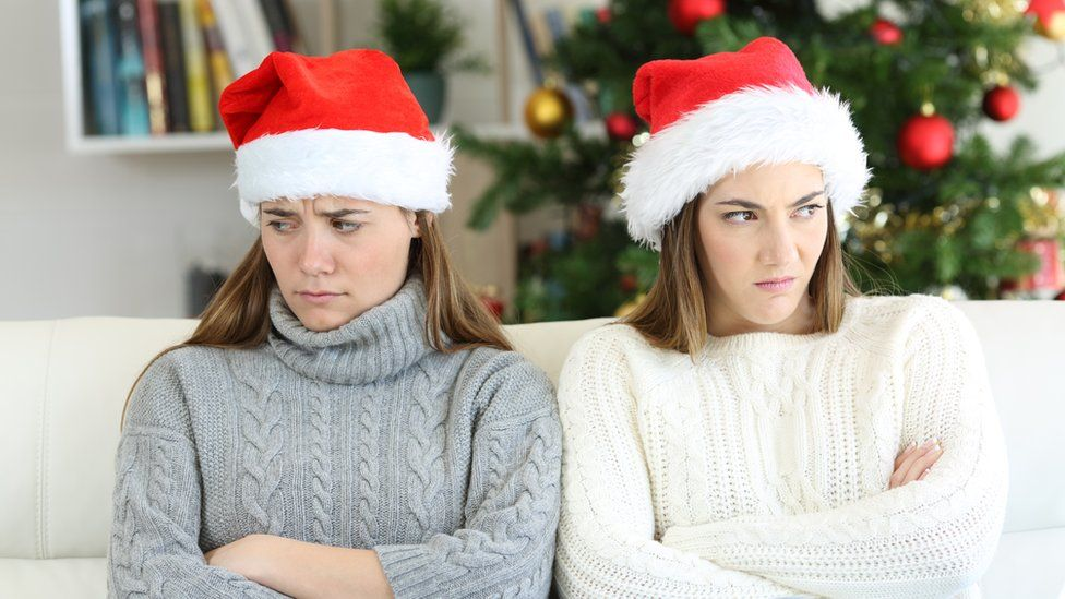 Two women wearing Santa hats looking away from each with a Christmas tree in the background