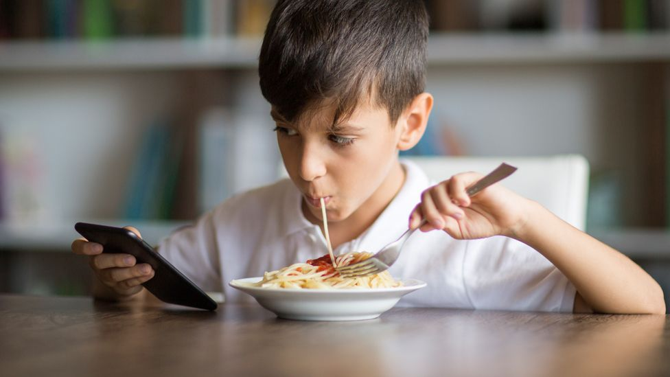 Boy eating and looking at a mobile phone
