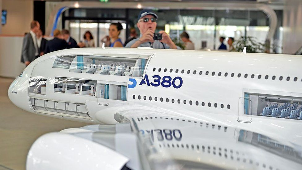 A visitor takes a photo of a model Airbus plane at the company's headquarters outside Toulouse