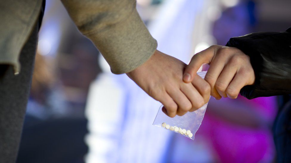 A stock image showing a clear bag containing drugs being exchanged