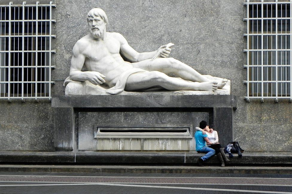 A sculpture and couple kissing