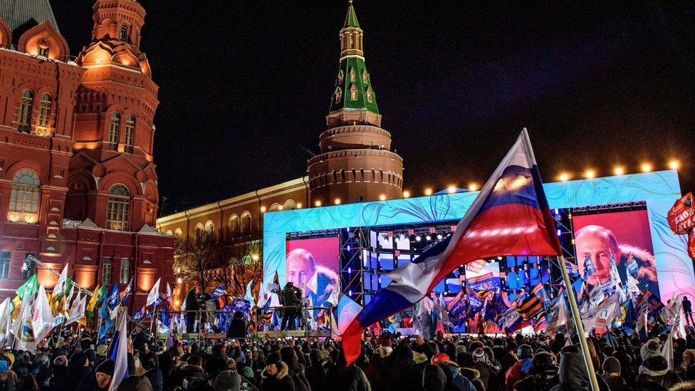 """People listen to presidential candidate, President Vladimir Putin during a rally and a concert celebrating the fourth anniversary of Russia""""s annexation of Crimea at Manezhnaya Square in Moscow on March 18, 2018."""