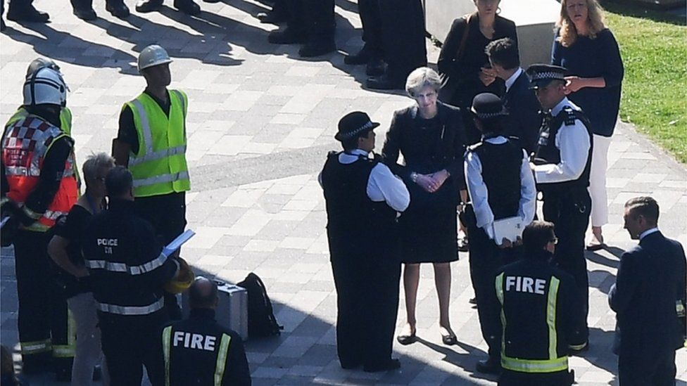 Theresa May meets fire fighters at the Grenfell Tower site