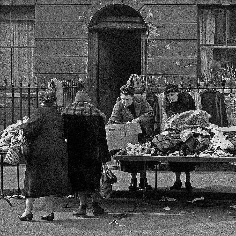 Market ladies sort the clothes in London's East End