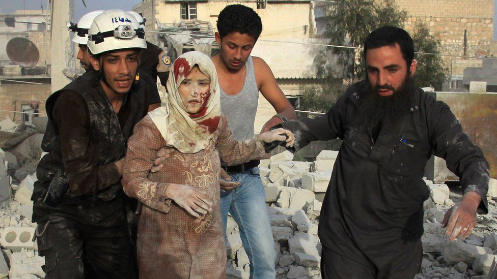 Syrian rescue workers and residents help an injured woman following a reported government air strike on the rebel-held Aleppo district of Haydariya on 10 April 2016