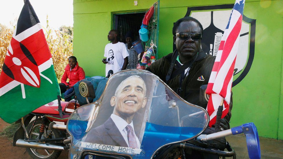 A Kenyan man sitting on a motorbike decorated with a poster of Barack Obama and the Kenyan and US flags, Kogelo, Kenya - Monday 16 July 2018