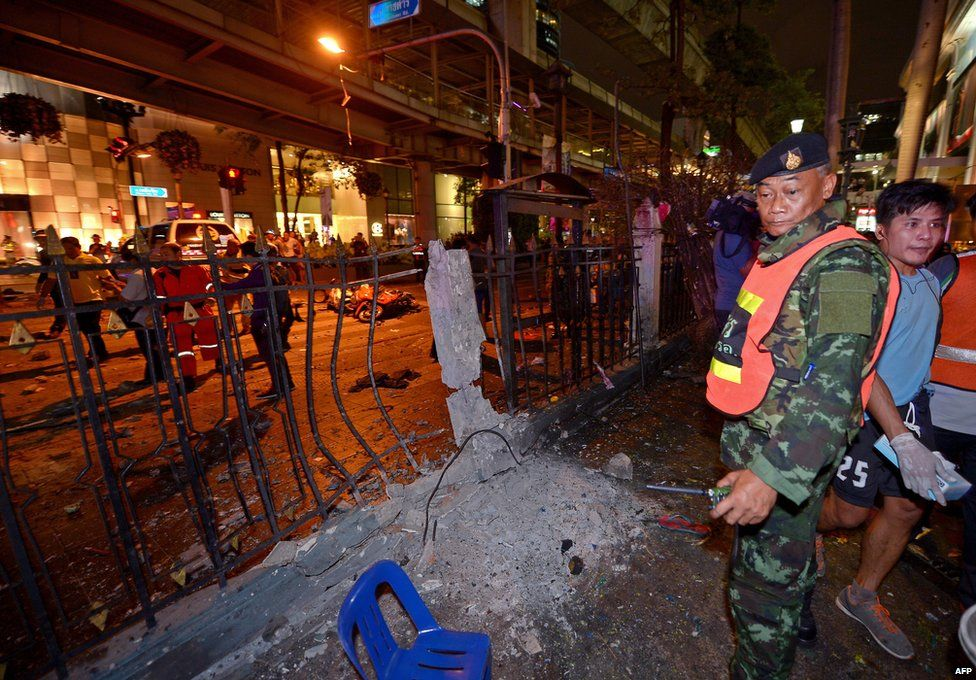 A Thai soldier (R) looks at the damage after a bomb exploded outside a religious shrine in central Bangkok late on 17 August 2015 killing at least 10 people and wounding scores more.