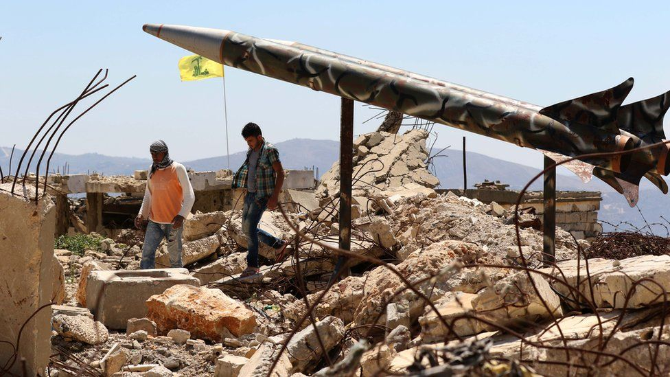 Youths walk past Hezbollah's mock rockets at the former Israeli-run prison of Khiam, which was destroyed in the 2006 war (12 July 2016)
