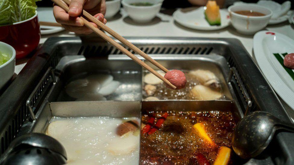 Customers eat hotpot in a Haidilao restaurant