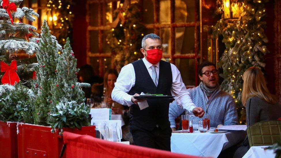 A waiter wearing a mask works at a restaurant in London