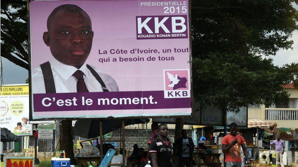 People pass a campaign poster of presidential candidate Kouadio Konan Bertin in Abidjan