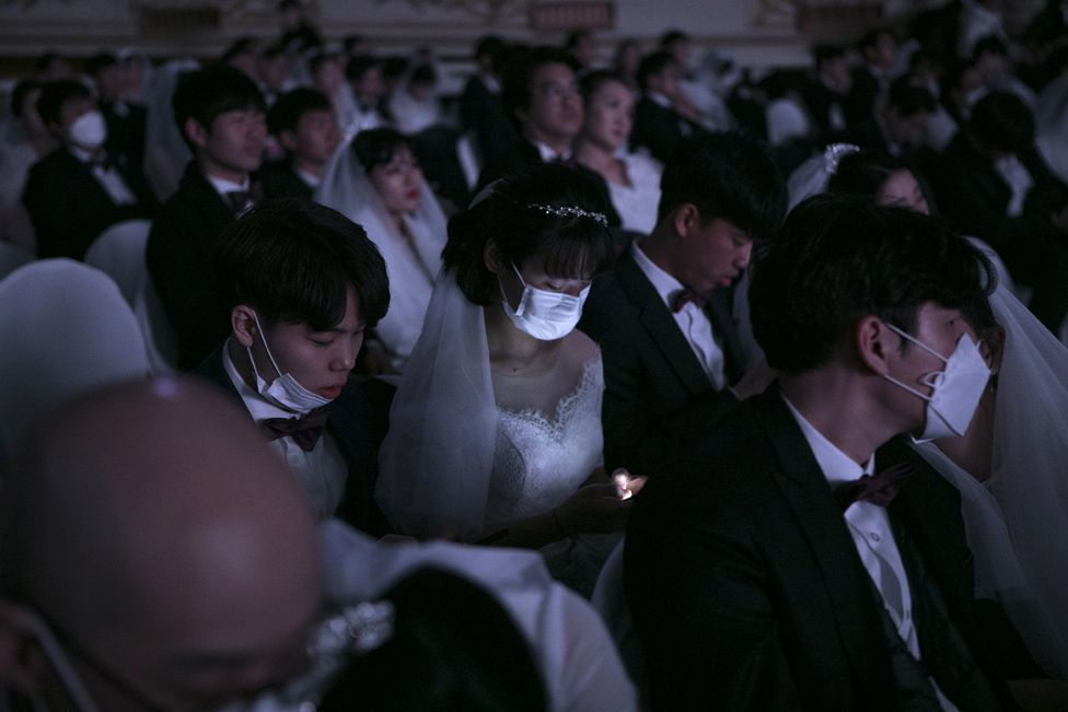A bride, wearing a mask, checks her phone during a mass wedding ceremony organised by the Unification Church in Gapyeong