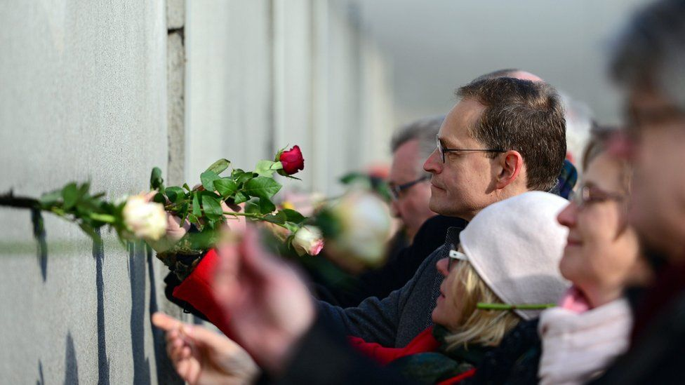 Berlin Mayor Michael Mueller places a rose in a crack during the central event to commemorate the 1989 Peaceful Revolution in the GDR.