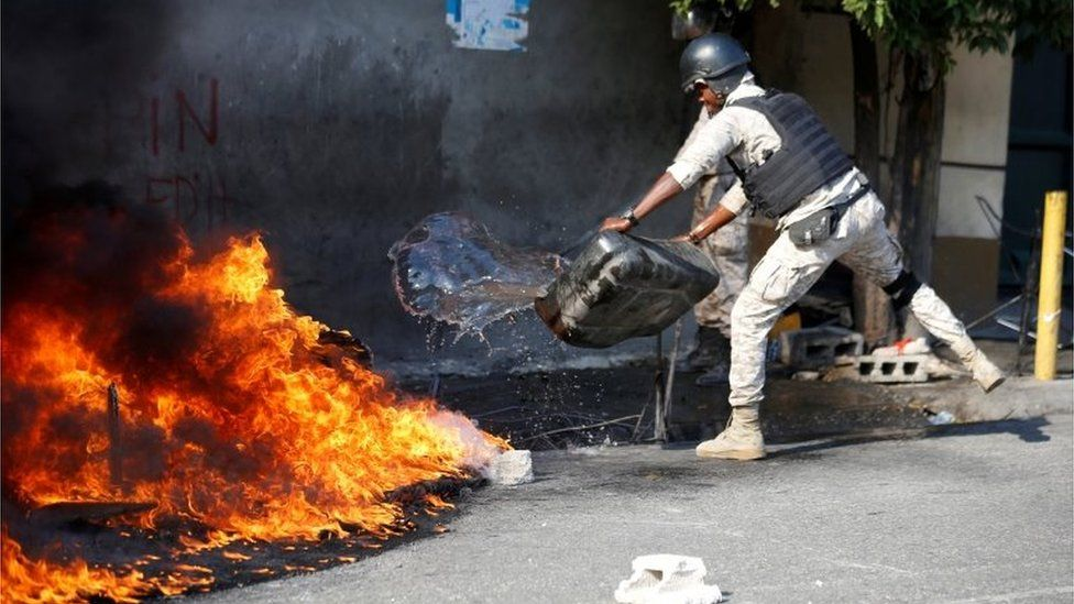A police officer puts out a burning fire as demonstrators take part in a protest against Haiti's President Jovenel Moïse, in Port-au-Prince, Haiti February 14, 2021.