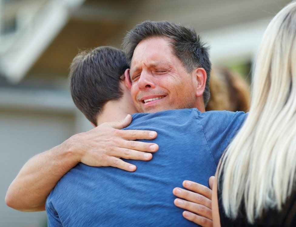 Don Damond hugs a neighbour after reading a statement about his fiancé