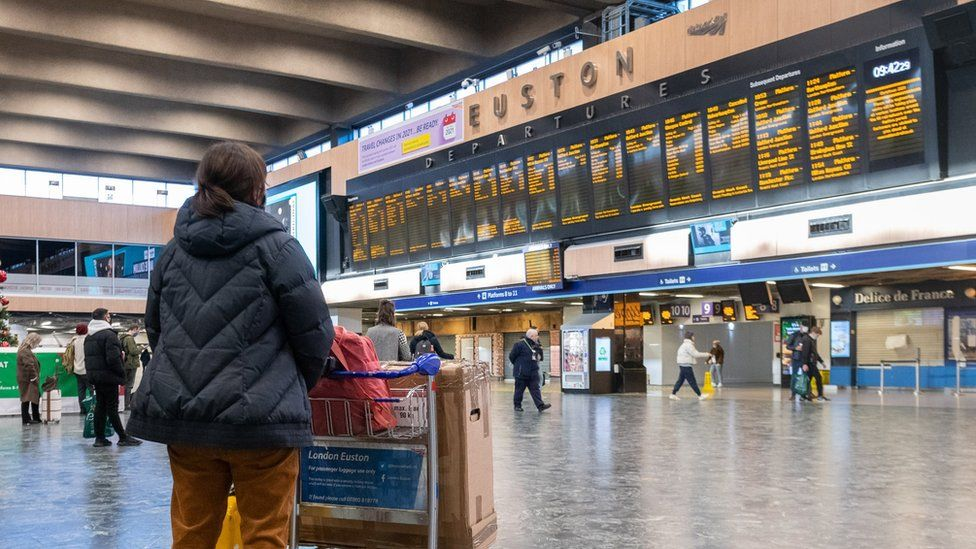 Passengers at Euston Station wait to find out if their trains are running on time as they prepare to leave the capital on December 19, 2020 in London