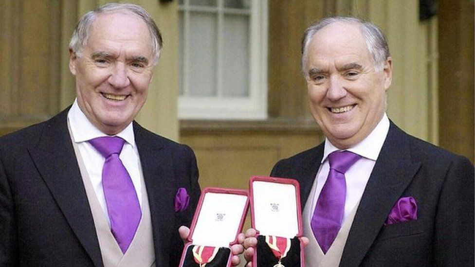 Sir David Barclay (L) and his twin brother Sir Frederick posing after receiving their knighthoods from the Queen at Buckingham Palace