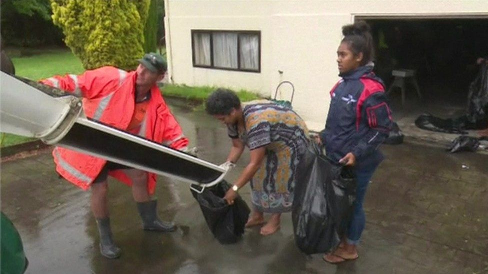 Residents fill bags with sand in preparation for possible flooding as a result of storm Gita, 20 February 2018