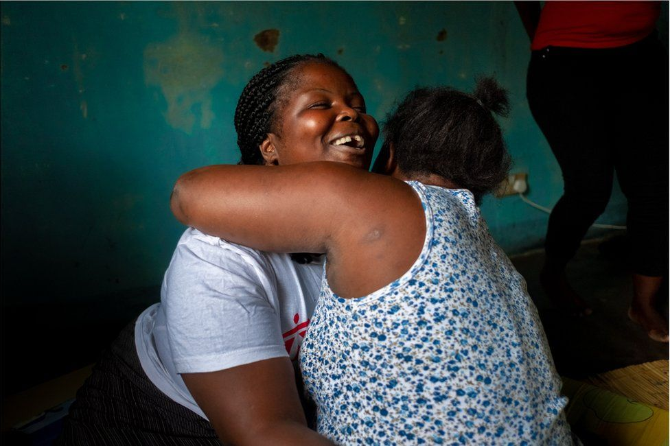 A woman hugging another woman