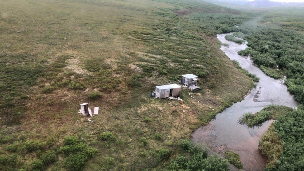 Aerial view of shack encampment by a river where the man signalled for help