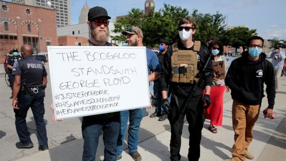 """Armed men, one carrying a sign reading """"The Boogaloo stands with George Floyd"""", are seen as protesters rally against the death in Minneapolis police custody of George Floyd, in Detroit, Michigan (May 30, 2020)"""