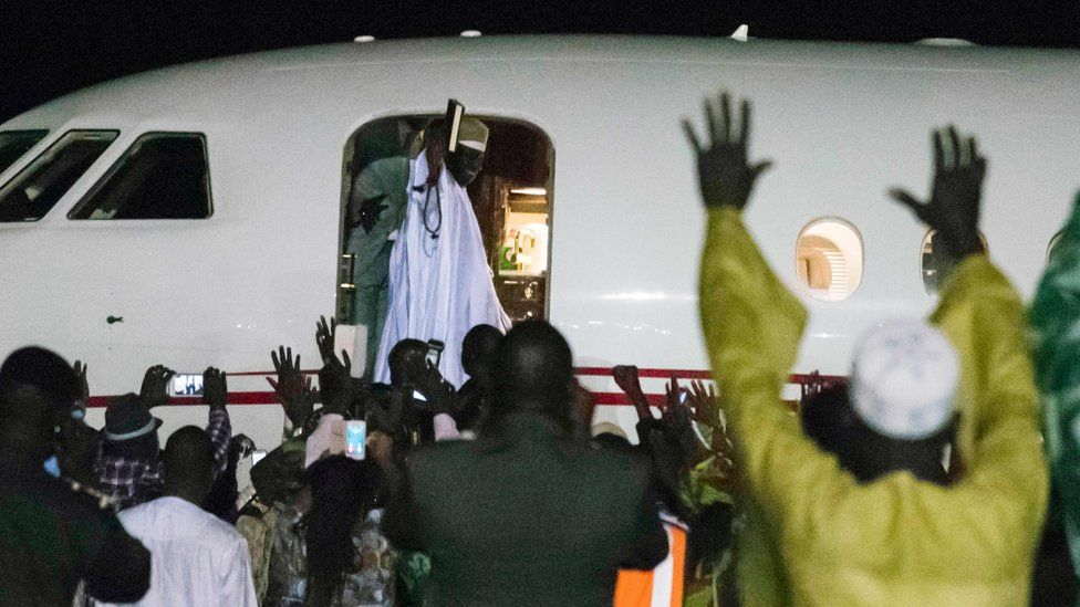Former president Yaya Jammeh, the Gambia's leader for 22 years, waves from the plane as he leaves the country on 21 January 2017 in Banjul